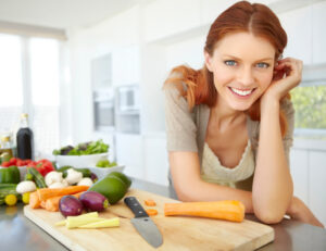Frau kocht mit Gemüse